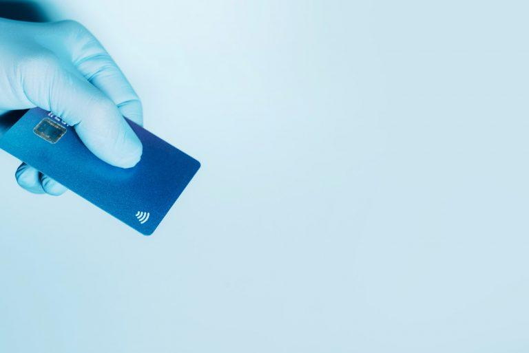 Contactless payment concept, copy space. Hand in protective gloves holding credit card with